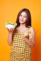 Healthy  Asian woman with measuring tape and salad.
