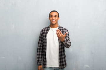 Young african american man with checkered shirt inviting to come with hand. Happy that you came