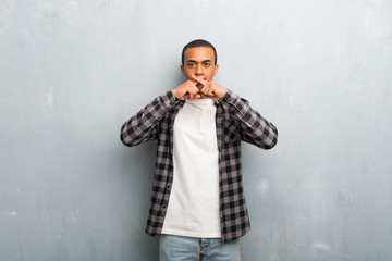 Young african american man with checkered shirt showing a sign of silence gesture