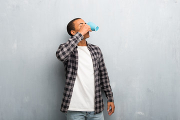 Young african american man with checkered shirt drinking hot coffee