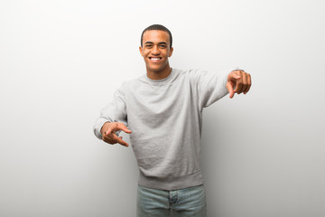 African american man on white wall background points finger at you while smiling