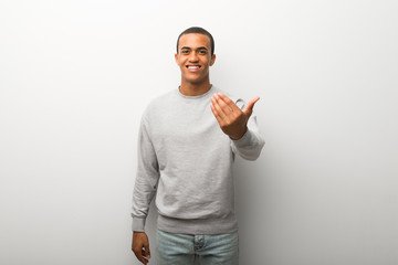 African american man on white wall background inviting to come with hand. Happy that you came