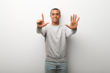 African american man on white wall background counting seven with fingers