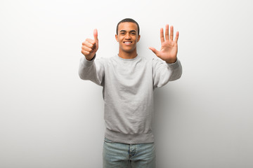 African american man on white wall background counting six with fingers