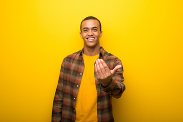 Young african american man on vibrant yellow background inviting to come with hand. Happy that you came