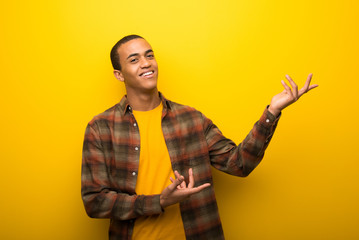 Young african american man on vibrant yellow background extending hands to the side for inviting to come