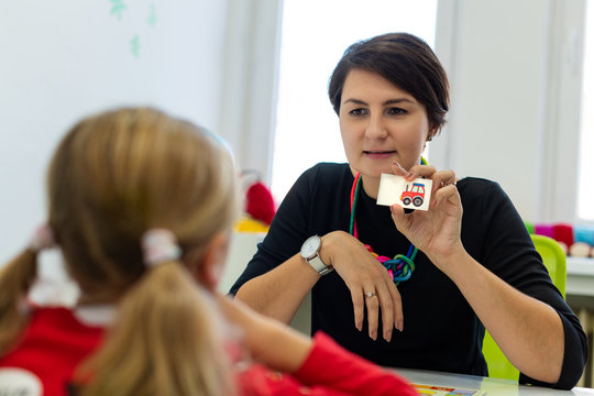 Elementary Age Girl in Child Occupational Therapy Session Doing Playful Exercises With Her Therapist.