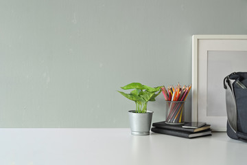 Contemporary workspace plant, mockup poster, bag and copy space.