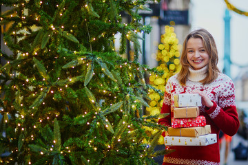 Happy young girl in holiday sweater with pile of Christmas presents