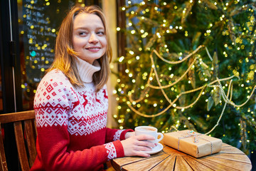 girl in holiday sweater drinking coffee or hot chocolate in cafe decorated for Christmas