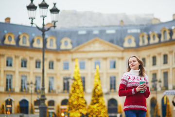 Girl walking with hot drink to go on a street of Paris decorated for Christmas