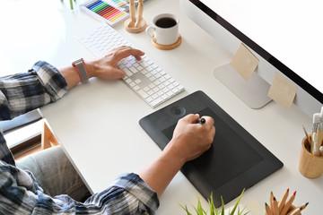 Graphic designer using digital tablet with desktop computer in studio office