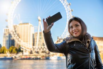 Attraktive, reisende Frau macht ein Selfie von sich auf einer Sightseeing Tour in London, England