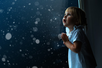 child looks out the window on Christmas day