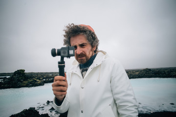 Concentrated creative content creator, videographer or photographer makes video or photo on action camera attached to gimball stabilizator on windy and cloudy day in iceland