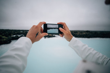 Adventurer tourist or travel blogger makes photos of blue lagoon sulfur geothermal turquoise water spa in iceland on smartphone