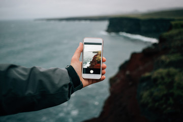 Adventurer, hiker or tourist holds out smartphone with photograph of amazing epic rough and beautiful icelandic landscape. Travel blogger or social media influencer explores place less travelled