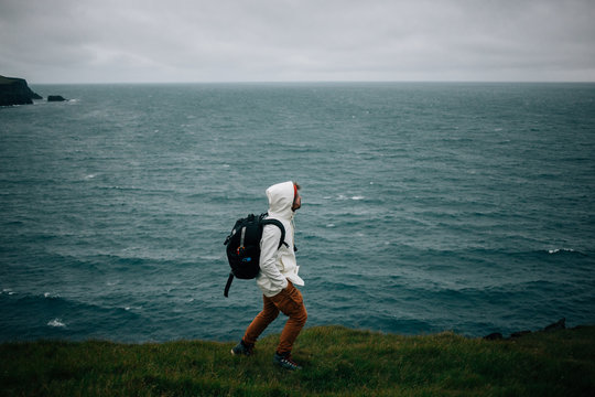 Adventurer, explorer and creative freelance nature photographer walks in icelandic landscape in waterproof rain gear, carries drone backpack. Explore more and wanderlust lifestyle