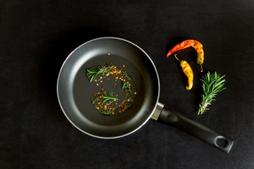 Frying pan with spices on a black background. Concept- cooking, menu, recipes.