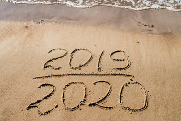 New Year 2019 is coming concept - inscription 2019 and 2020 on a beach sand