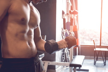Muscular builder asian man training his body with lifting dumbbell on right hand.