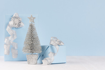 Christmas decorative silver tree with gifts and ribbons on white wood table and pastel blue wall.