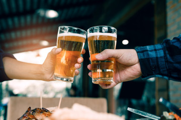 Close up of hand people friends toasting and clinking with glass of beer in restaurant.