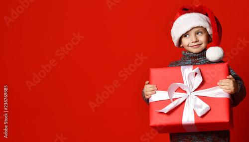 a842b2559857a Smiling funny child in Santa red hat holding Christmas gift in hand.  Christmas concept.