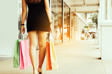 Rear view of women walking at shopping outlet and holding shopping bags.