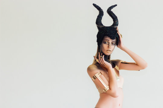 The model wears a hat of Maleficent and has makeup in the Halloween theme. She is posing And there is space behind the text.