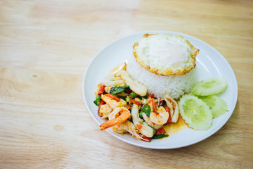 Rice topped with stir-fried Seafood and basil And fried eggs On the wood background.