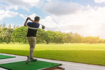 Golfer hitting golf shot with club on course at morning time.