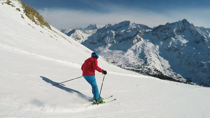 Wall Mural - Man skiing on the prepared slope with fresh new powder snow in Italian Alps, Tonale