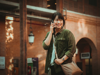 Asian woman using smartphone with happy mood in shopping mall