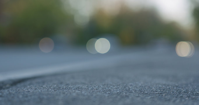 low angle shot of blurred moving cars on city street with closeup focus on sidewalk