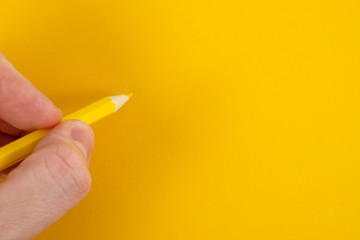 A hand is holding a yellow pencil on a yellow background close up. Copy space.