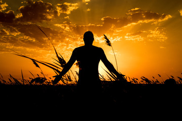Silhouette of man with their hands in the sunset. Outdoor shot