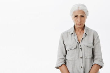 Indoor shot of sad and gloomy cute grandmother with gray hair frowning looking with puppy eyes at camera raising eyebrows hopefully feeling unhappy and lonely posing against white background
