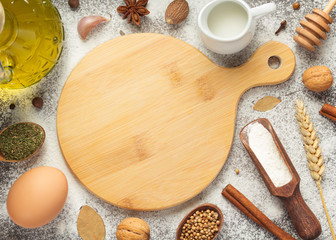 cutting board and bakery ingredients on wooden background