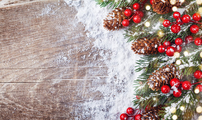 Christmas background with snowy fir branches, cones and bokeh lights. Holiday banner.