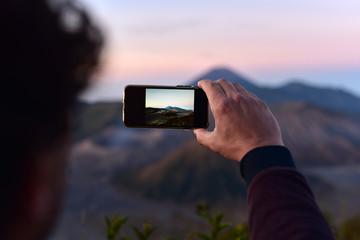 Tourist man taking the photos of Mount Bromo at sunrise, Java Island, Indonesia