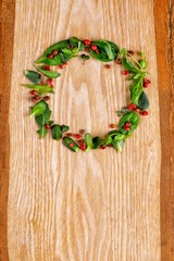 New Year's wreath from microgreen and pepper shinus on a wooden texture.