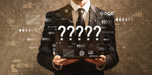 Question marks with businessman holding a tablet computer on a dark vintage background