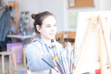 Girl artist paints a picture on canvas with brushes