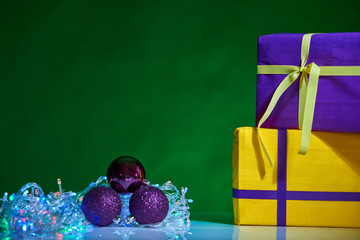 gorgeous design yellow and violet  Christmas boxes with decorations on green background