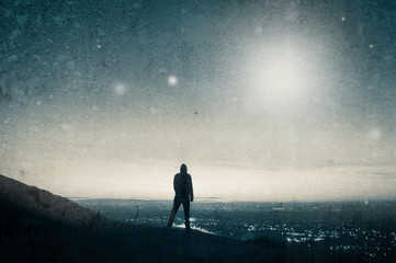 A lone hooded figure standing on hill looking at UFOs in the sky. With a grunge, vintage blue edit.