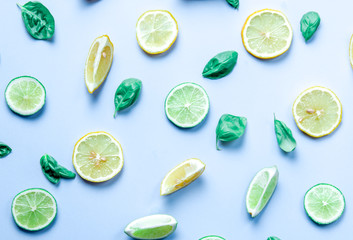 Above view at cutted lemons and limes on grey background
