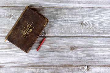 Catholic bible and red church nonflammable candle on wooden background with copy space