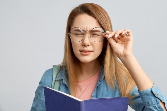 Beautiful young blonde girl holding glasses and squinting trying to read the inscription in front of her. Girl student with poor eyesight have difficulty reading small text