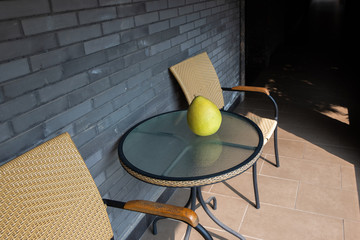 Large yellow fruit Pomelo. Fruit closeup lies on the glass table. Gray brick wall. Big beautiful Pomelo.